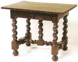 Table avec pieds torses et tiroirs avec une poignée tombante.